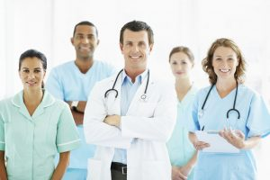 Portrait of a middle aged doctor with hands folded standing in front of his team